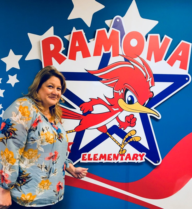 India Castro in front of a Ramona Elementary sign.