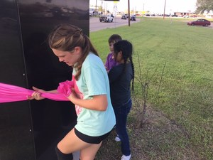 patti welder student council member tying pink ribbon around trees on campus in honor of breast cancer awareness month