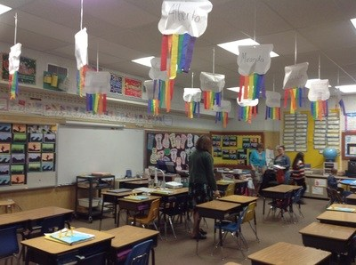 Classroom with multicolored student art hanging from the ceiling.