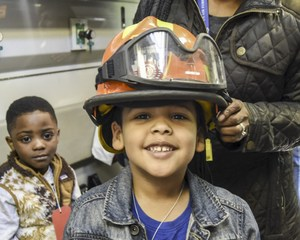 Young smiling preschooler wearing fire helmet