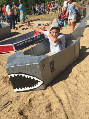 student sitting in shark cardboard boat on shore