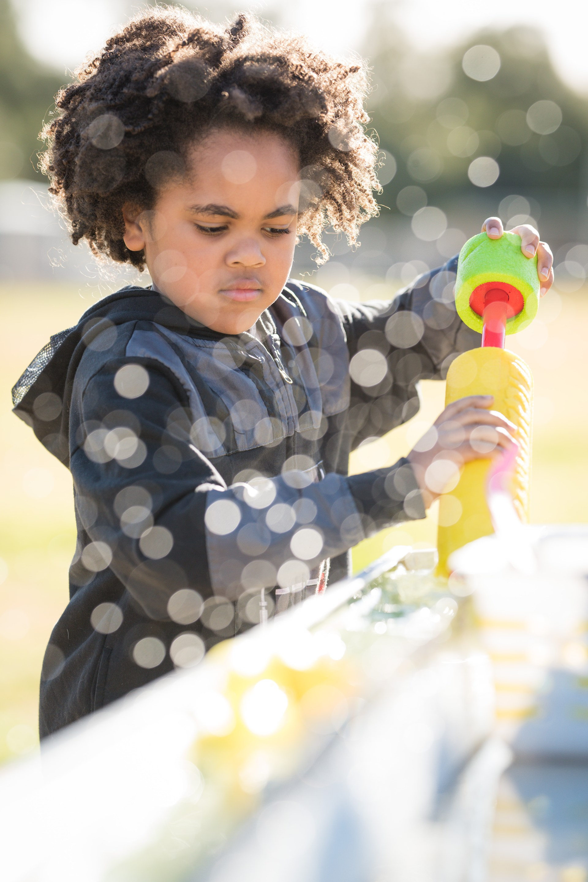 young boy playing with bubble blower