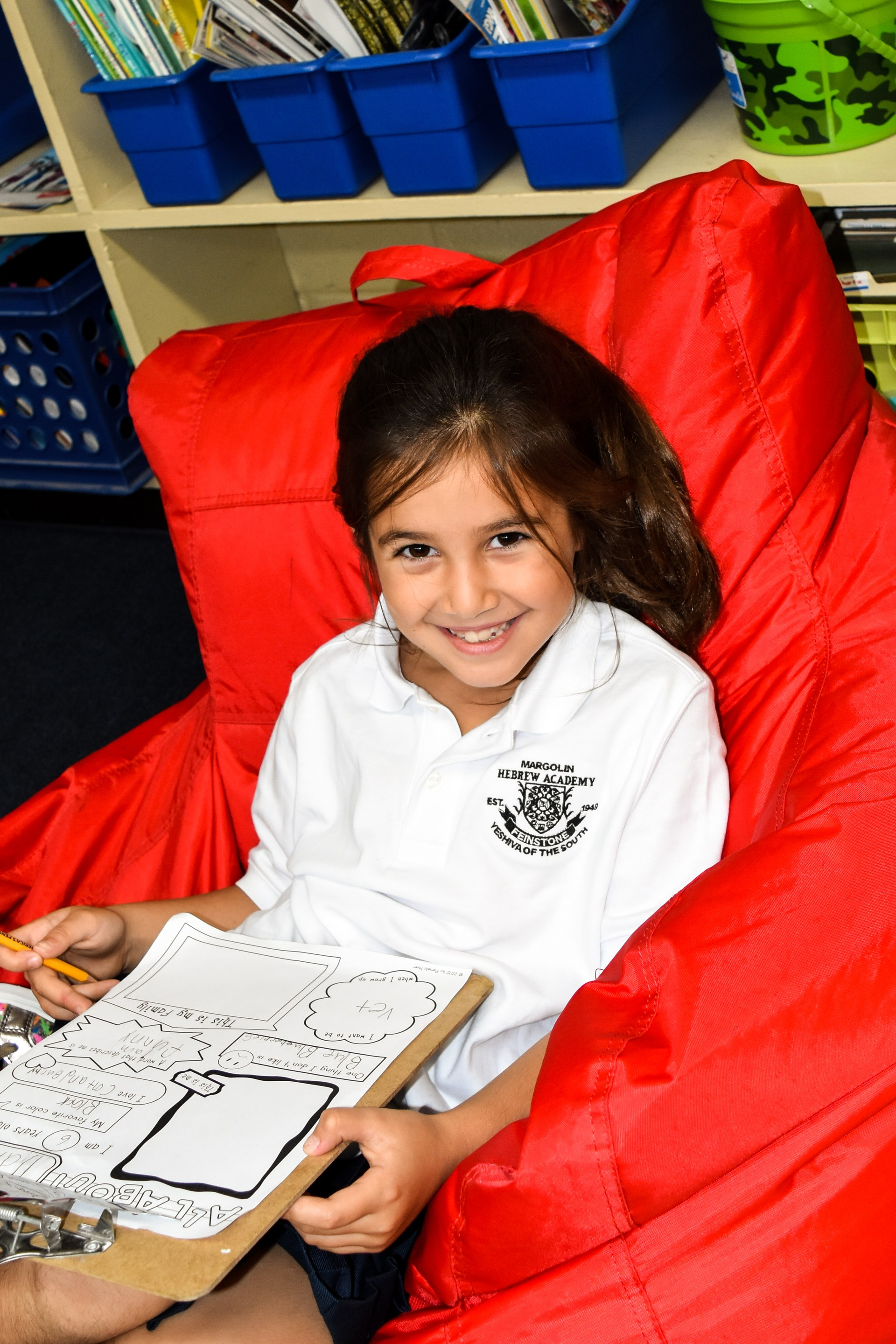 Girls sits in beanbag reading a book.