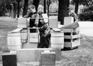 Children playing outside with boxes building.