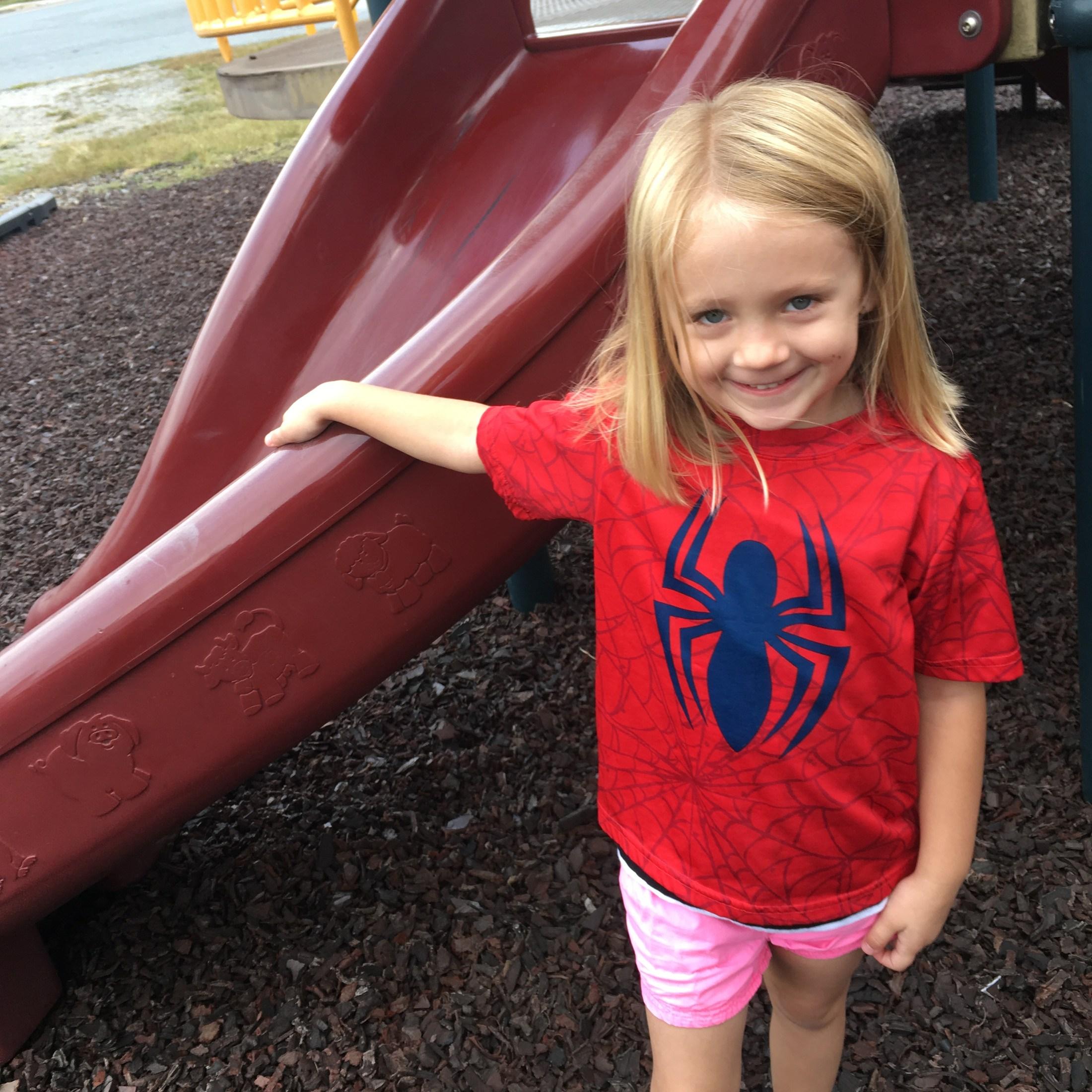 girl in spiderman tshirt on playground