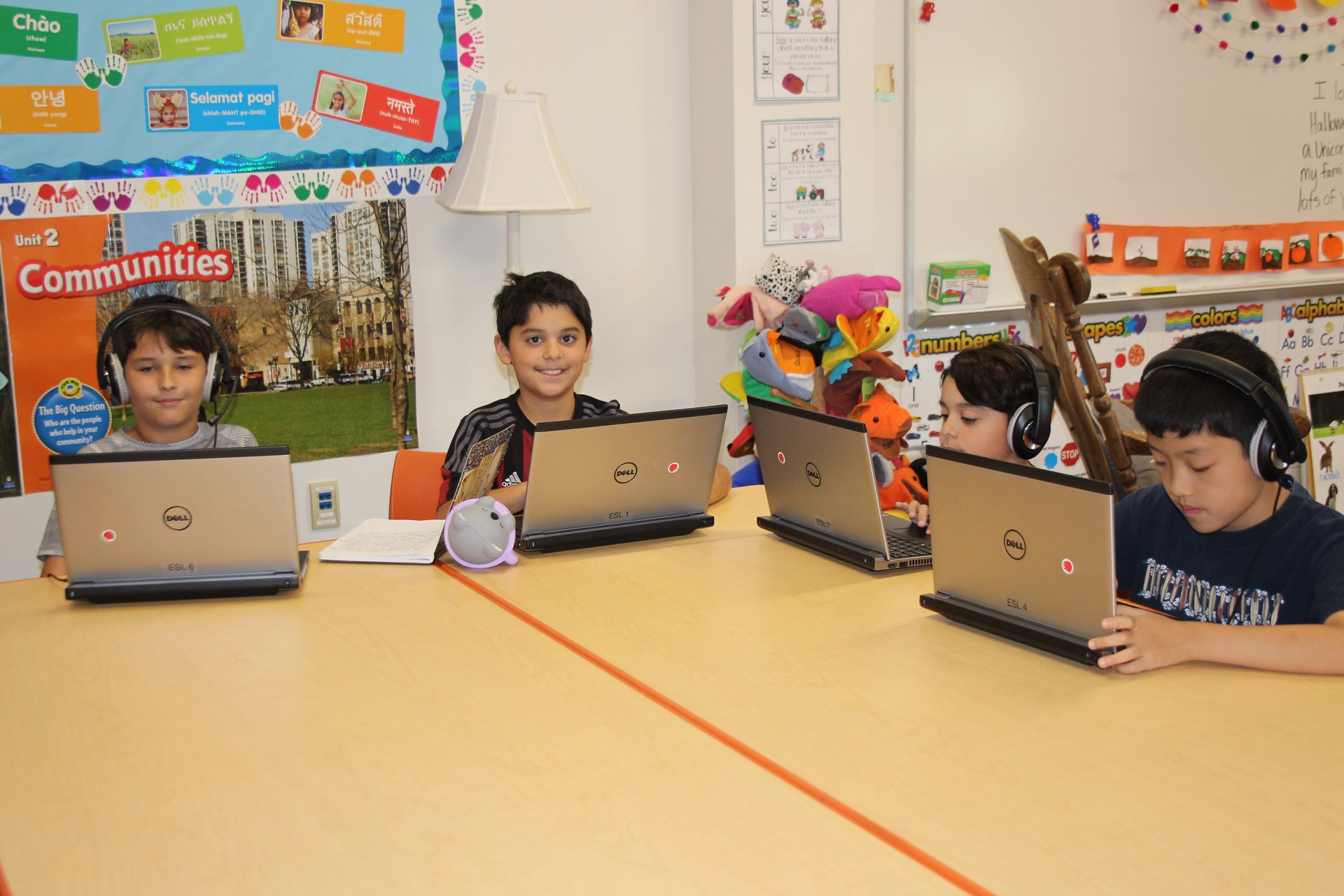 Four students work with computers and headsets during their lessons.