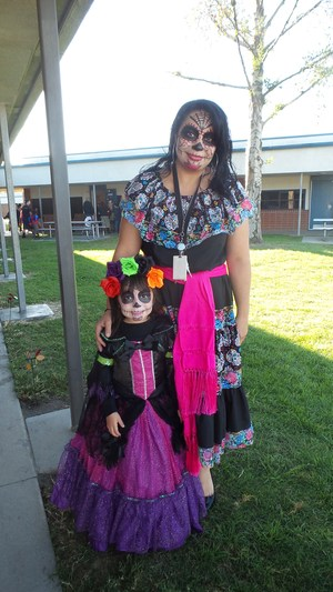 A teacher stands beside her student clothed in traditional holiday dresses and face paint at Tracy Elementary's Día de los Muertos celebration on Nov. 2.