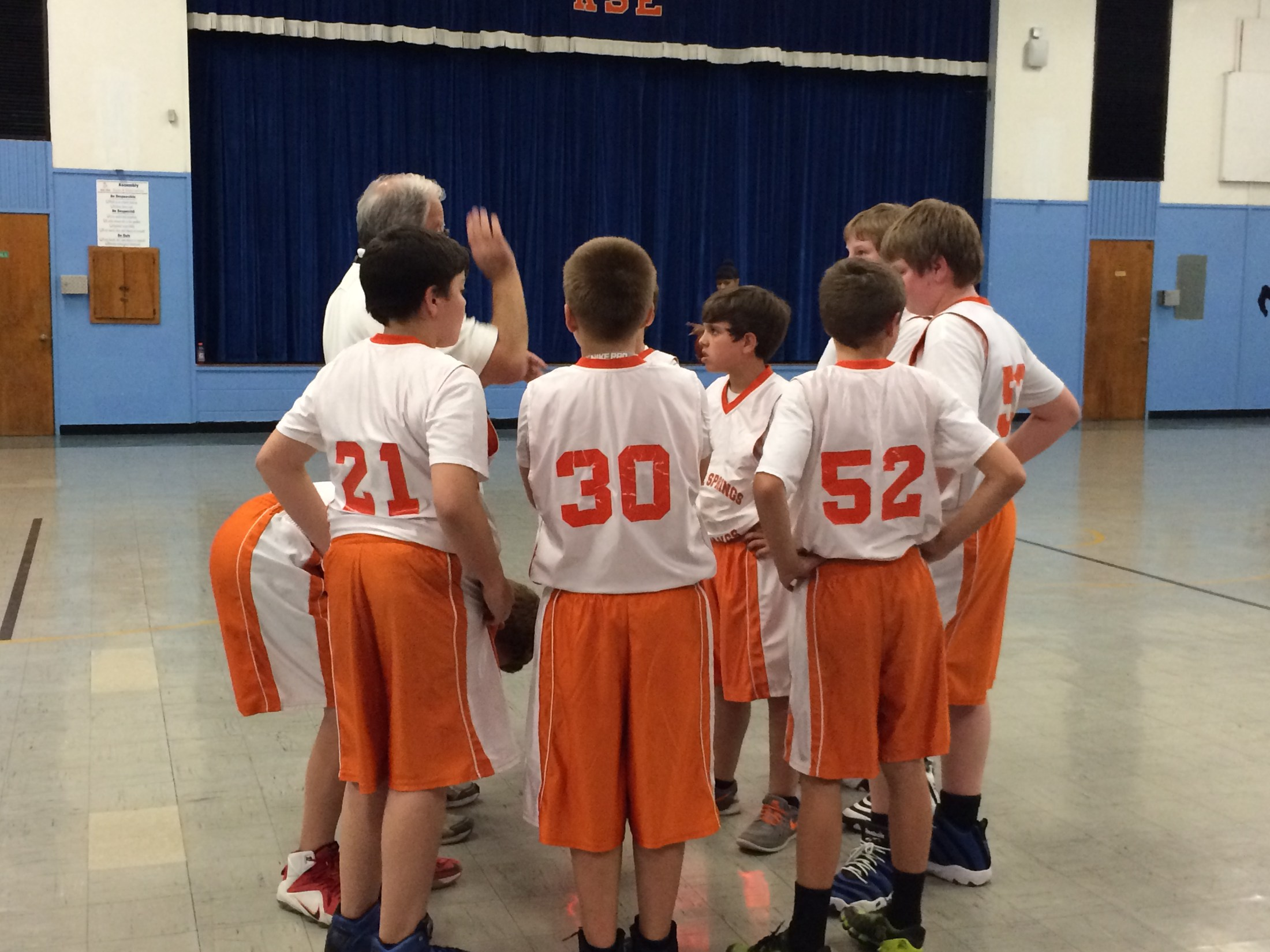 Boys with Coach huddle on court before game