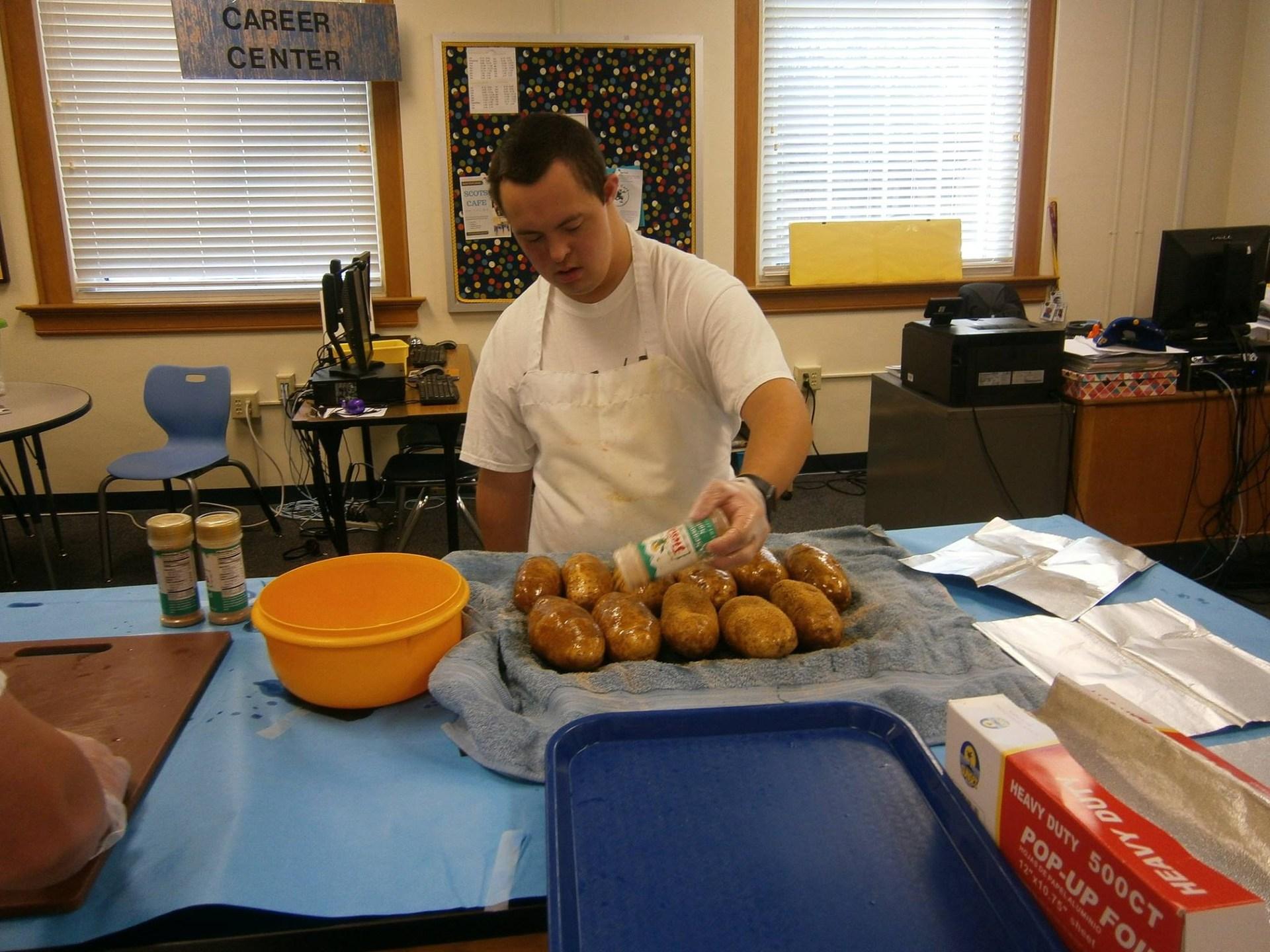 A Scot's Cafe employee seasons a mound of fresh baked potatoes.