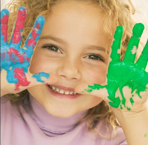 Image of young child showing painted hand palms.