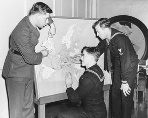 3 soldiers look at a raised map of Europe