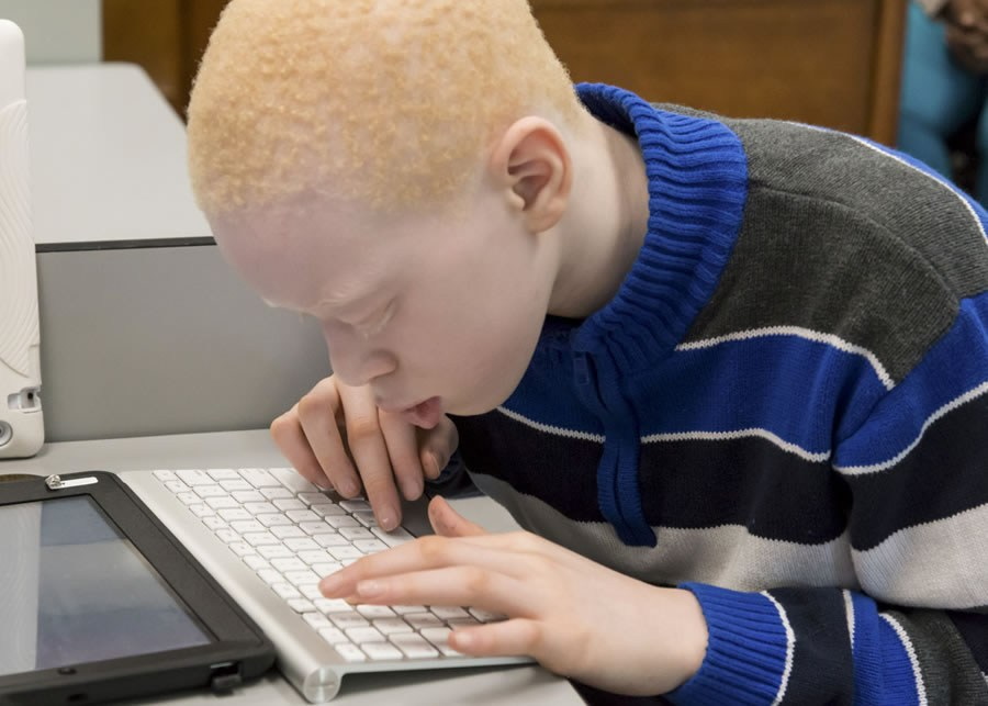 a student typing on a keyboard with his ipad