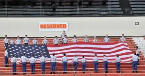 JROTC cadets holding large American flag in bleachers of Bulldog stadium
