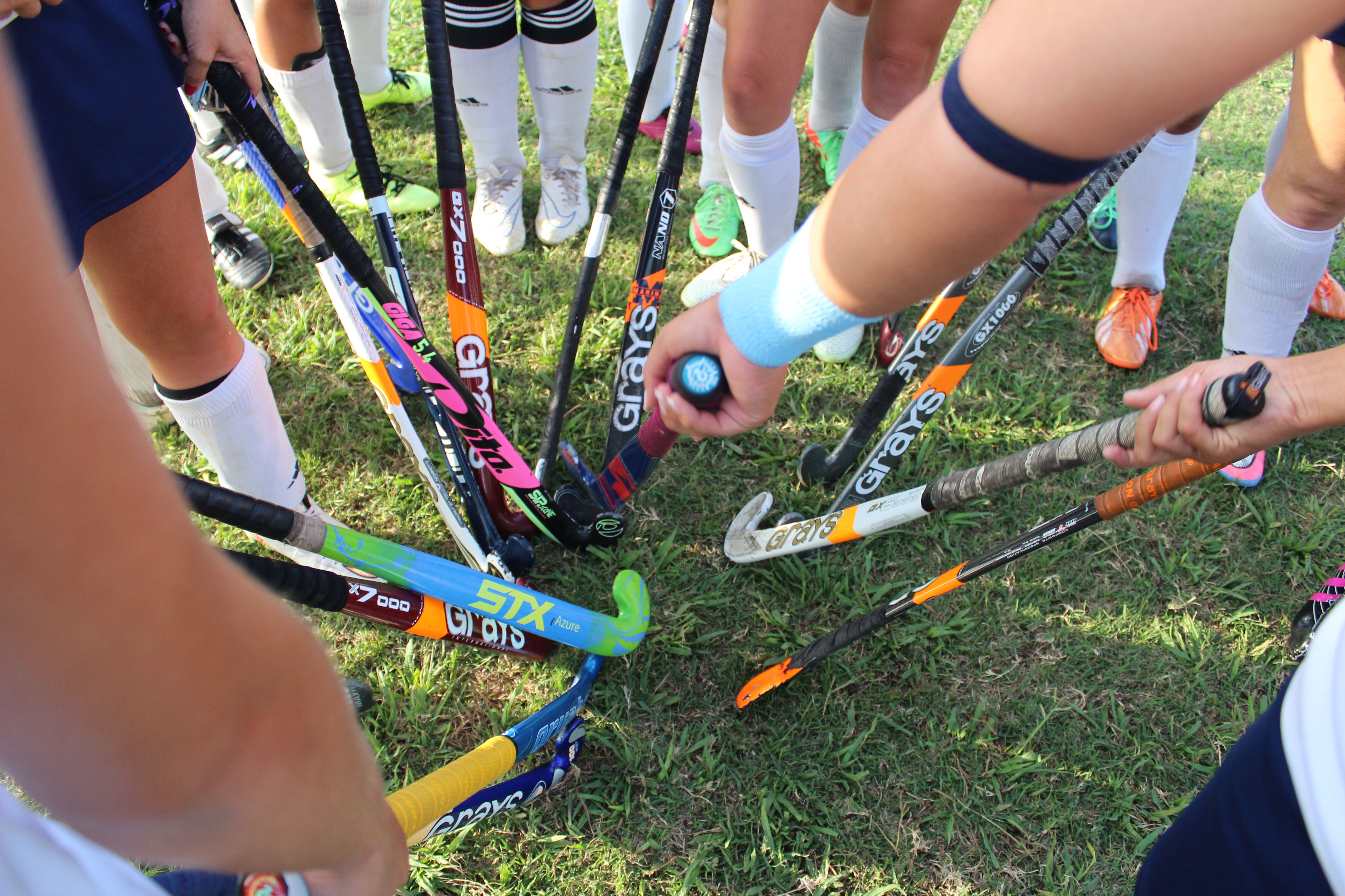 Girls field hockey sticks in a circle