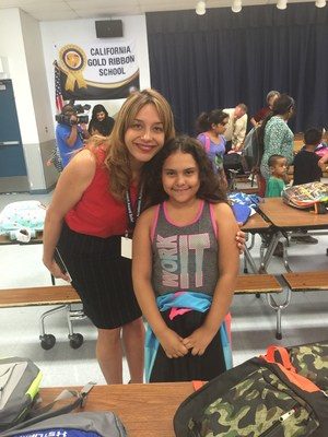 Abby Almandarez, a fifth-grader at Tracy Elementary School, stands with Principal Erika Valenzuela to show off the backpack she chose on Aug. 10. The pack, loaded with school supplies, was among 300 provided free through a partnership between the District and Kaiser Permanente Baldwin Park Medical Center.