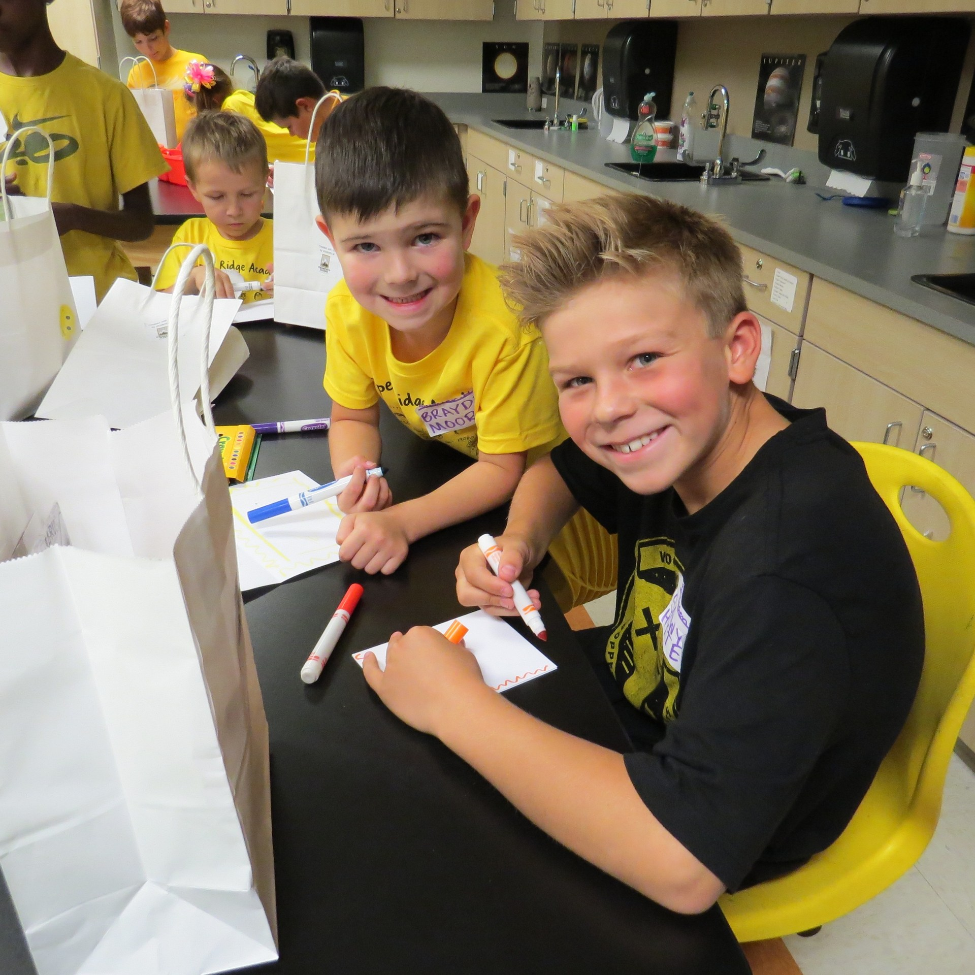 Two students take a break from writing on cards to smile at the camera