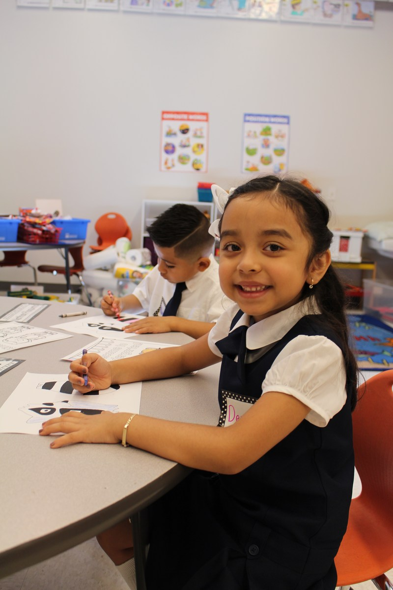 Female kindergarten student coloring in class.