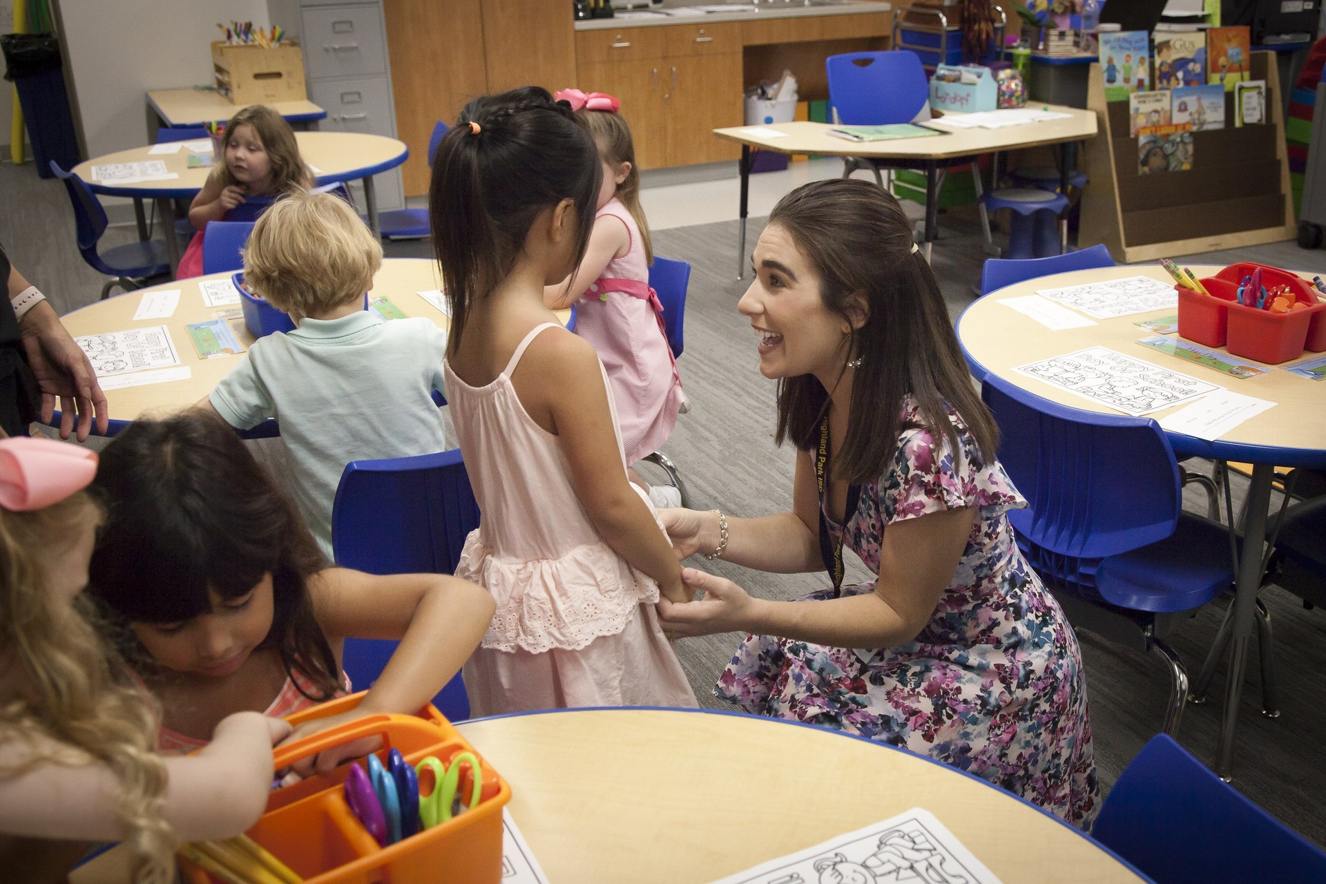 An elementary school teacher visits with a student in the classroom