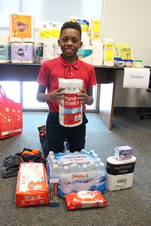 Male student holding paper towels water and diapers and other essentials home items purchased for hurricane relief