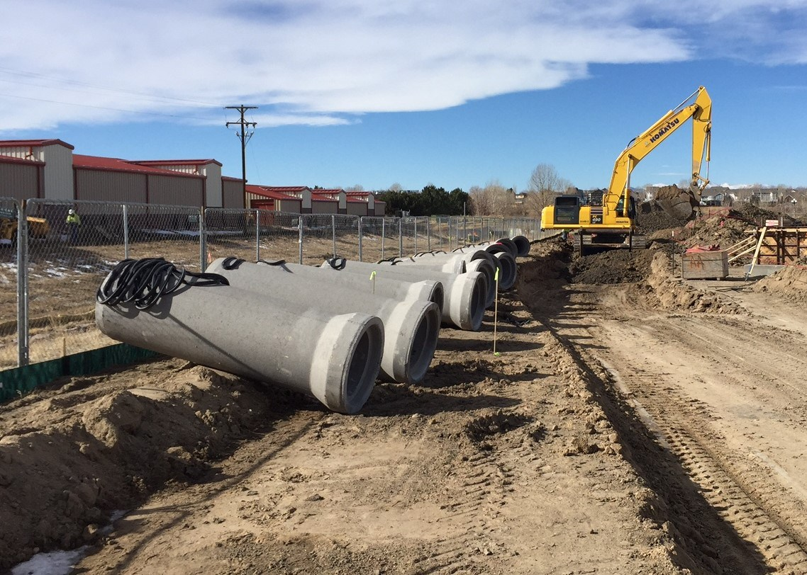 Large concrete pipes lay on the ground