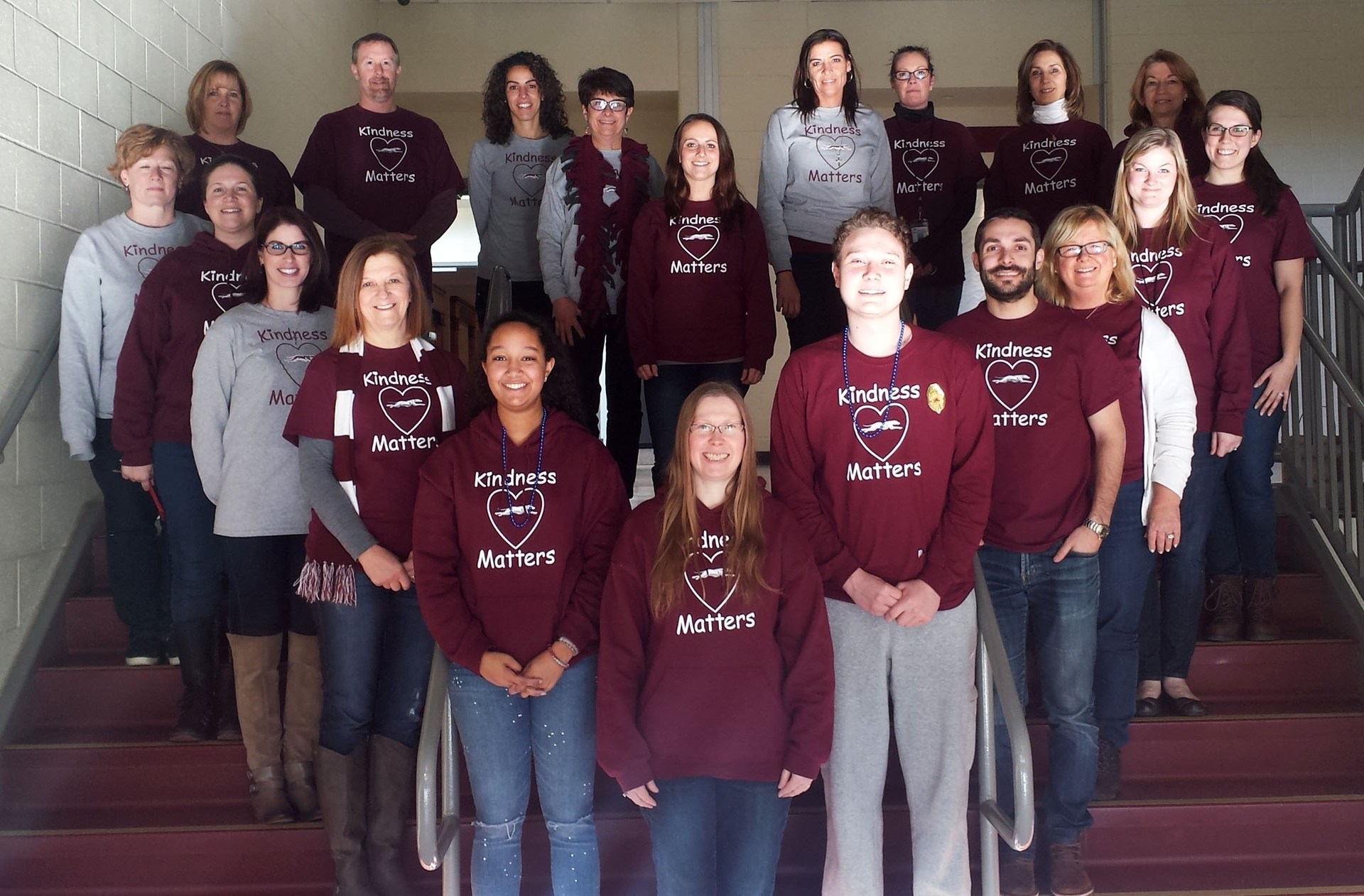 Students and teachers wearing kindness t-shirts form a heart on the stairs at Naugatuck High School