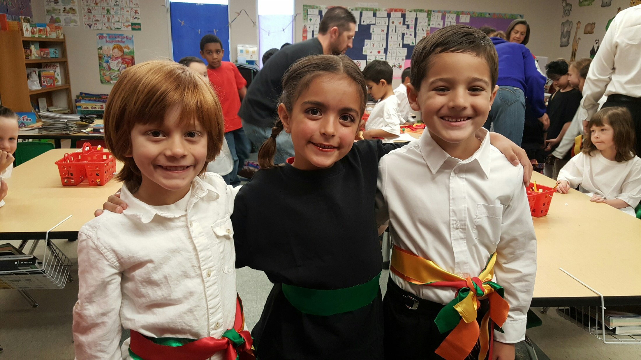 Two boys and one girl student wearing colorful heritage sashes during International Day