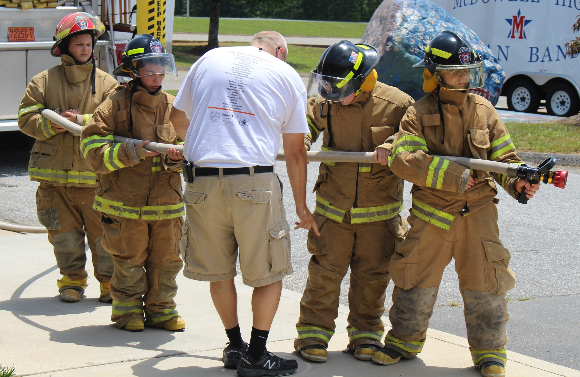 Students in fire gear learning about firefighting