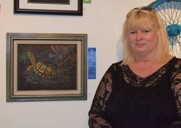 Mrs. Musick standing beside one of her award winning artworks titled called home that shows a box turtle disappearing.  The turtle is under a bush and by a fence as he is looking over his shoulder, parts of him are just line work to show he is disappearing.