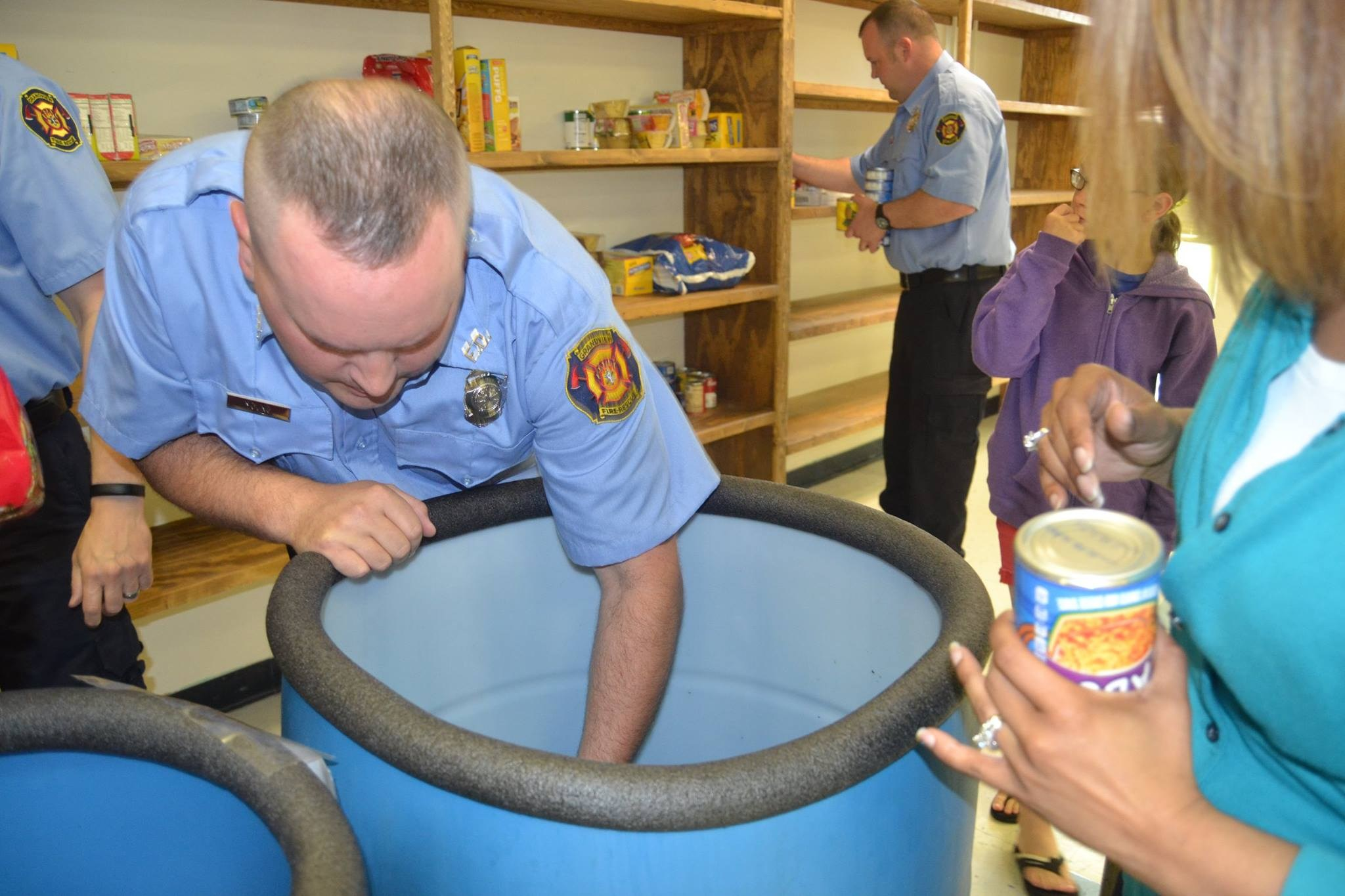 Firefighter emptying a blue barrel of food for High Grove families