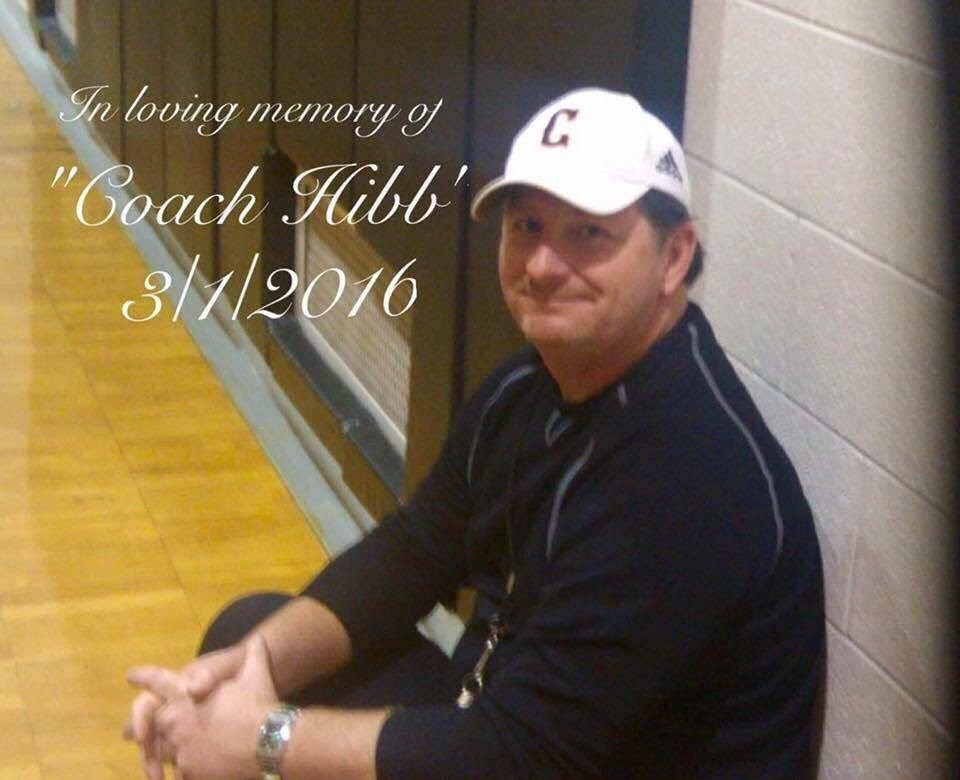 Photo of former coach Hibb sitting near basketball court
