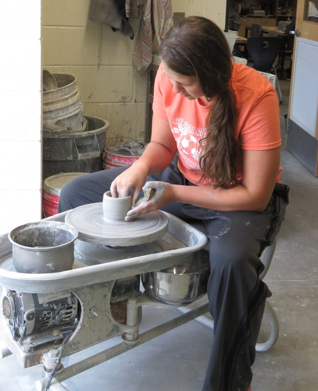 A TKHS art student works on a pottery project.