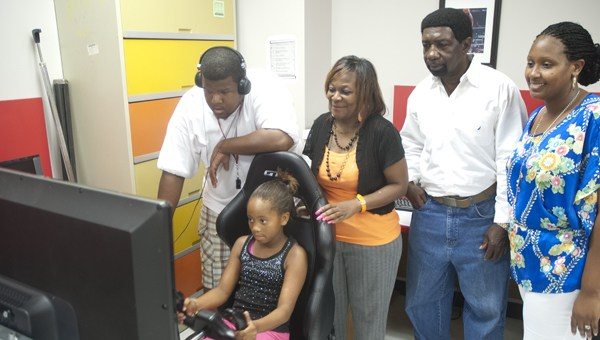 Young girl and 3 adults around flight simulator computer