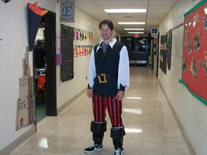 A teacher dressed as a pirate is standing in the hall.