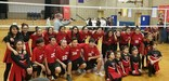 Tamayo volleyball team posing in front of the net.