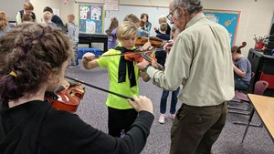 Students try their hands at playing the violin.