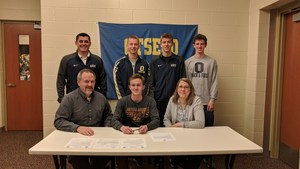 Will Finch, with his parents and Coach, signs his letter of intent to run at CMU.