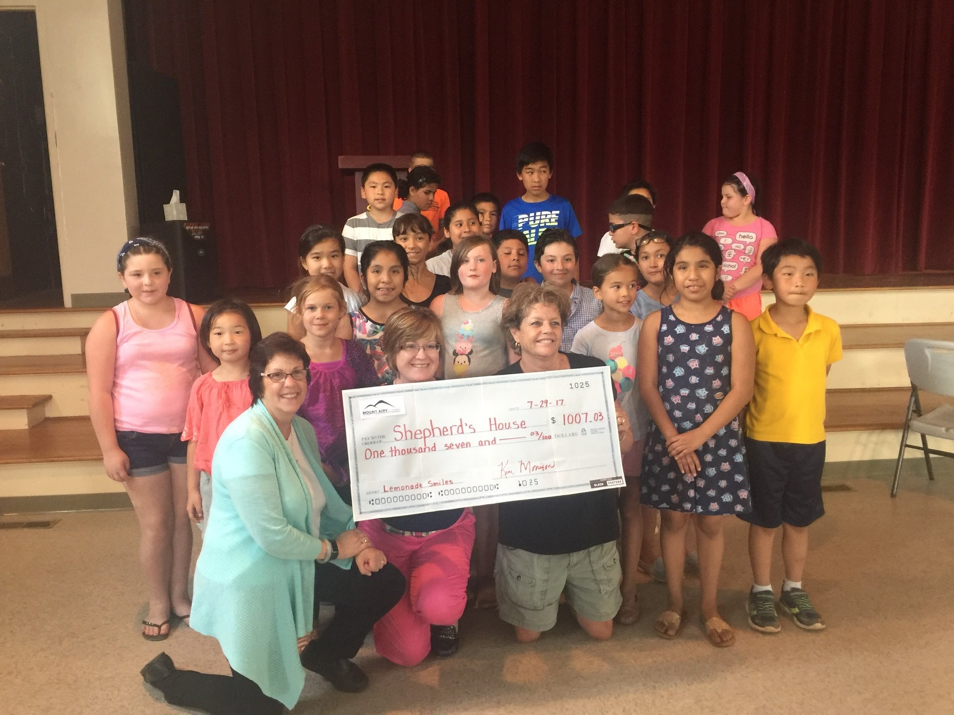 Students present a check to a local charity