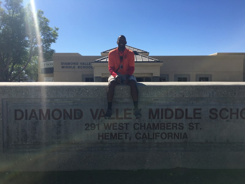 Kristopher Brooks sitting on top of a Diamond Valley sign.