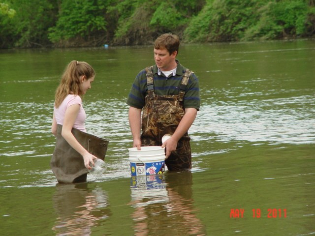Student and teacher collecting water samples from the Rouge River.