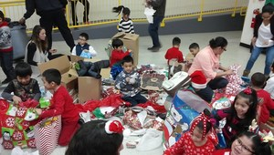 Kindergarten students opening their gifts from Santa