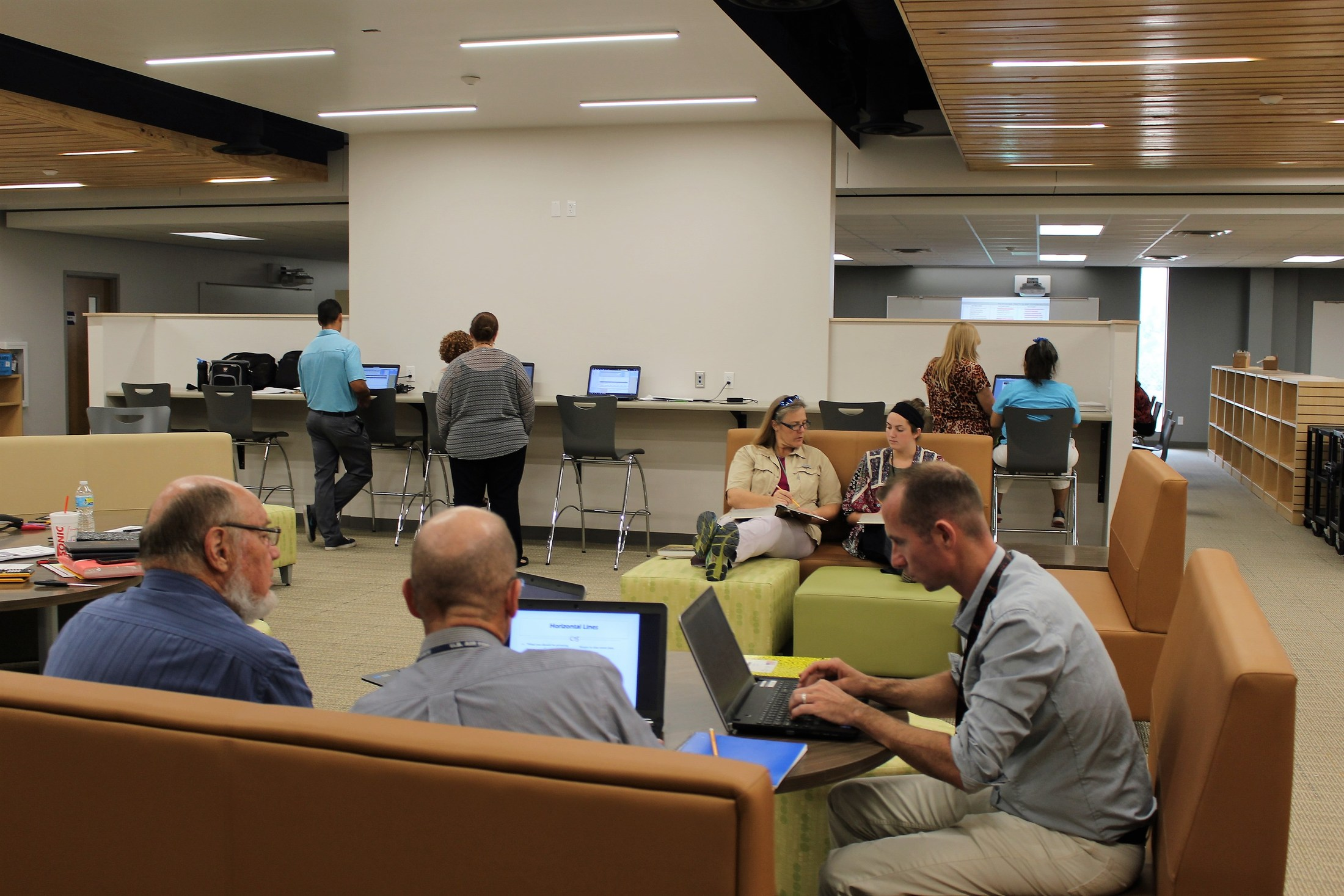 Adults working in groups in the library.