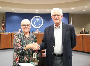 Janet Mendoza shaking hands with Governing Board Trustee Gene Hikel.