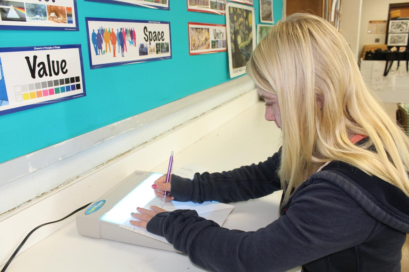 Kelsey Bell uses the tracing light on a drawing project