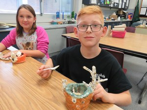 Ian Cappon takes a scoop of ice cream from his handmade bowl made to look like a deer with a broken antler.