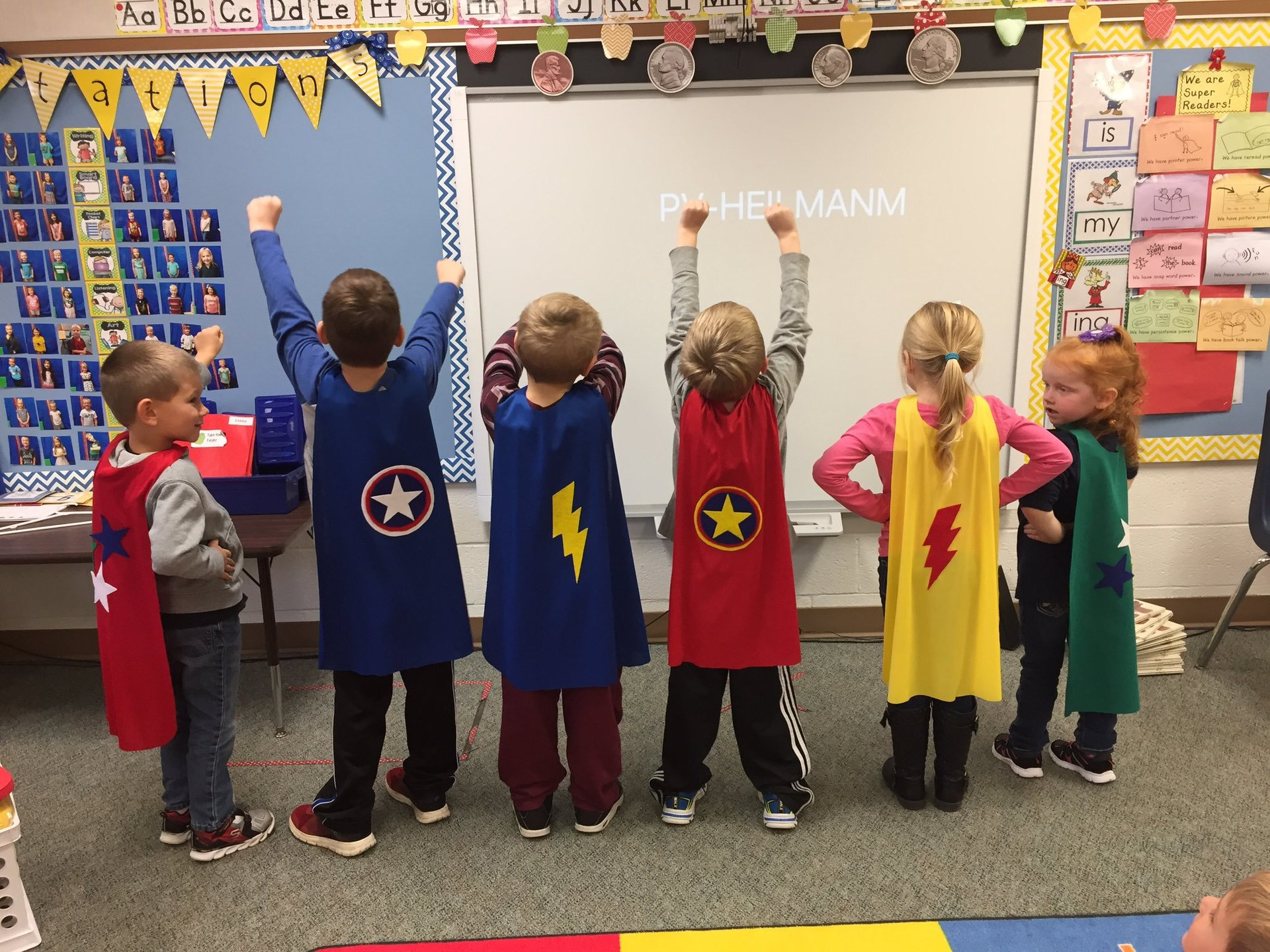 Six young students in superhero capes are engaged in learning at the whiteboard in the classroom.