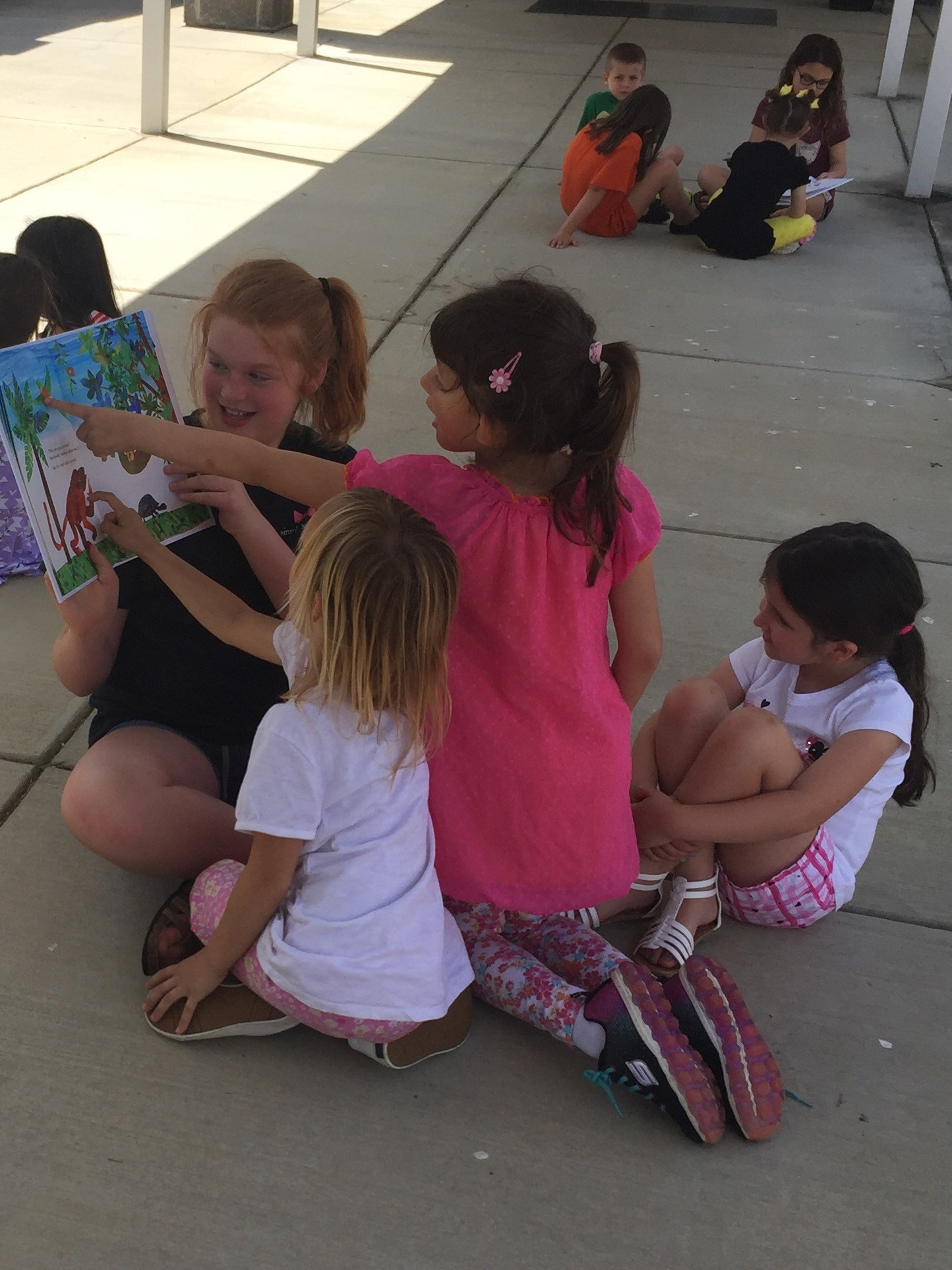 Student reading to younger students.