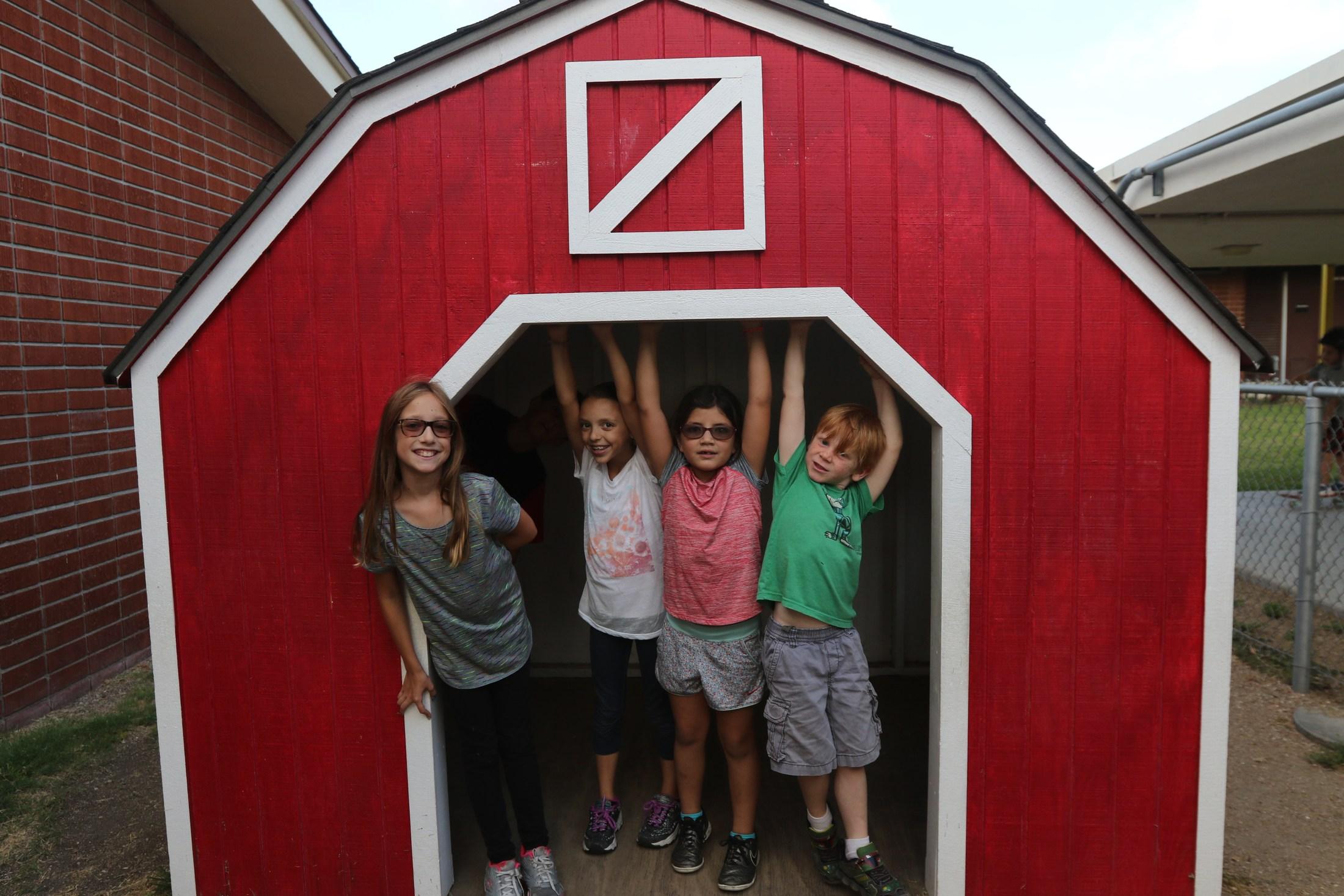 a group of children in the kindergarten yard barn