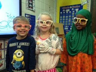 Three students wearing multicolored glasses smiling at the camera.