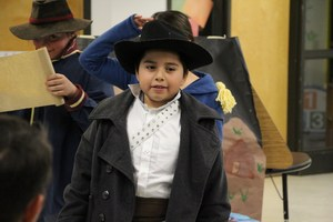 A student pretends to be an early American explorer at night at the museum.