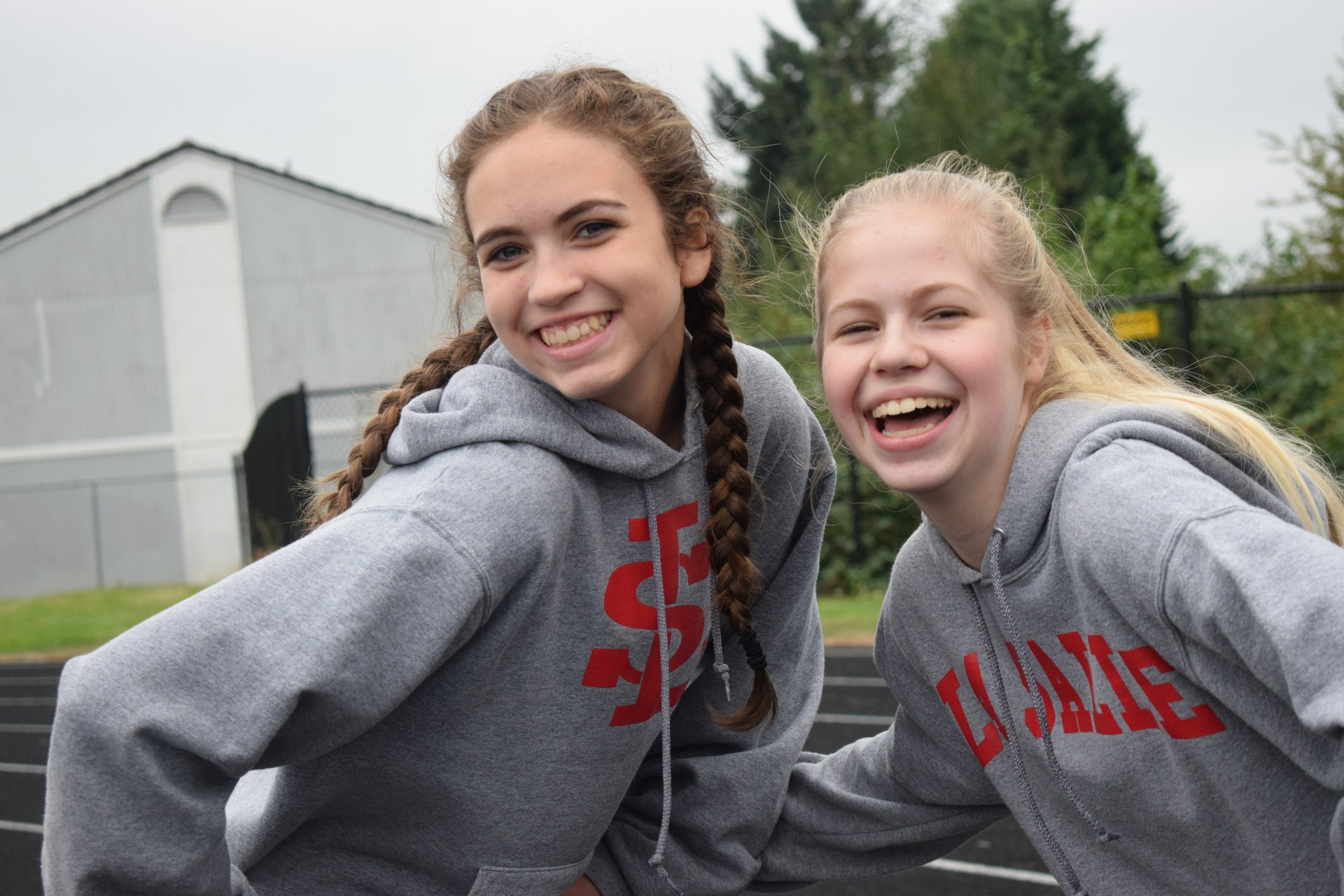Two girls smiling while standing on the track.